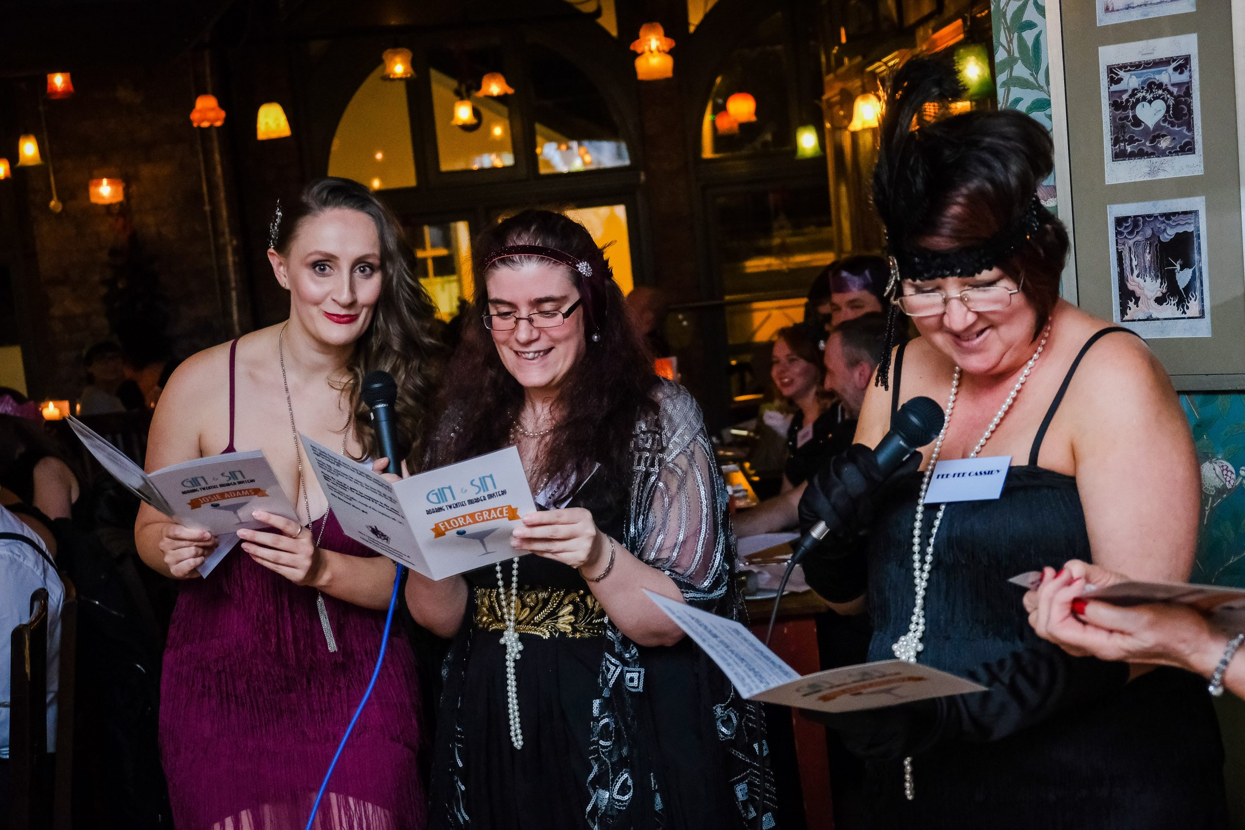 Party guests reading out murder mystery scripts